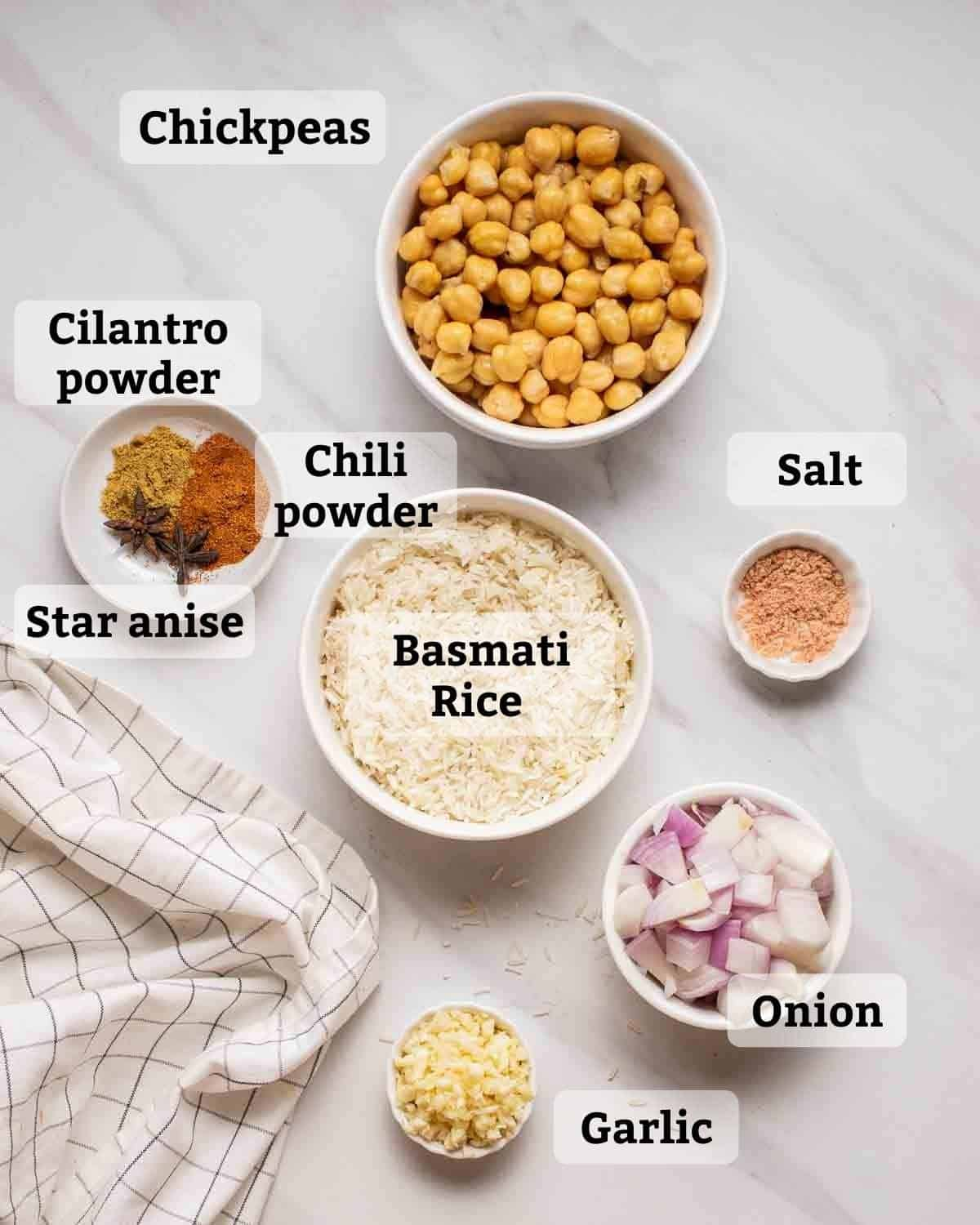 Ingredients needed like rice, chickpeas, onion, garlic and spices on a white marbled background.