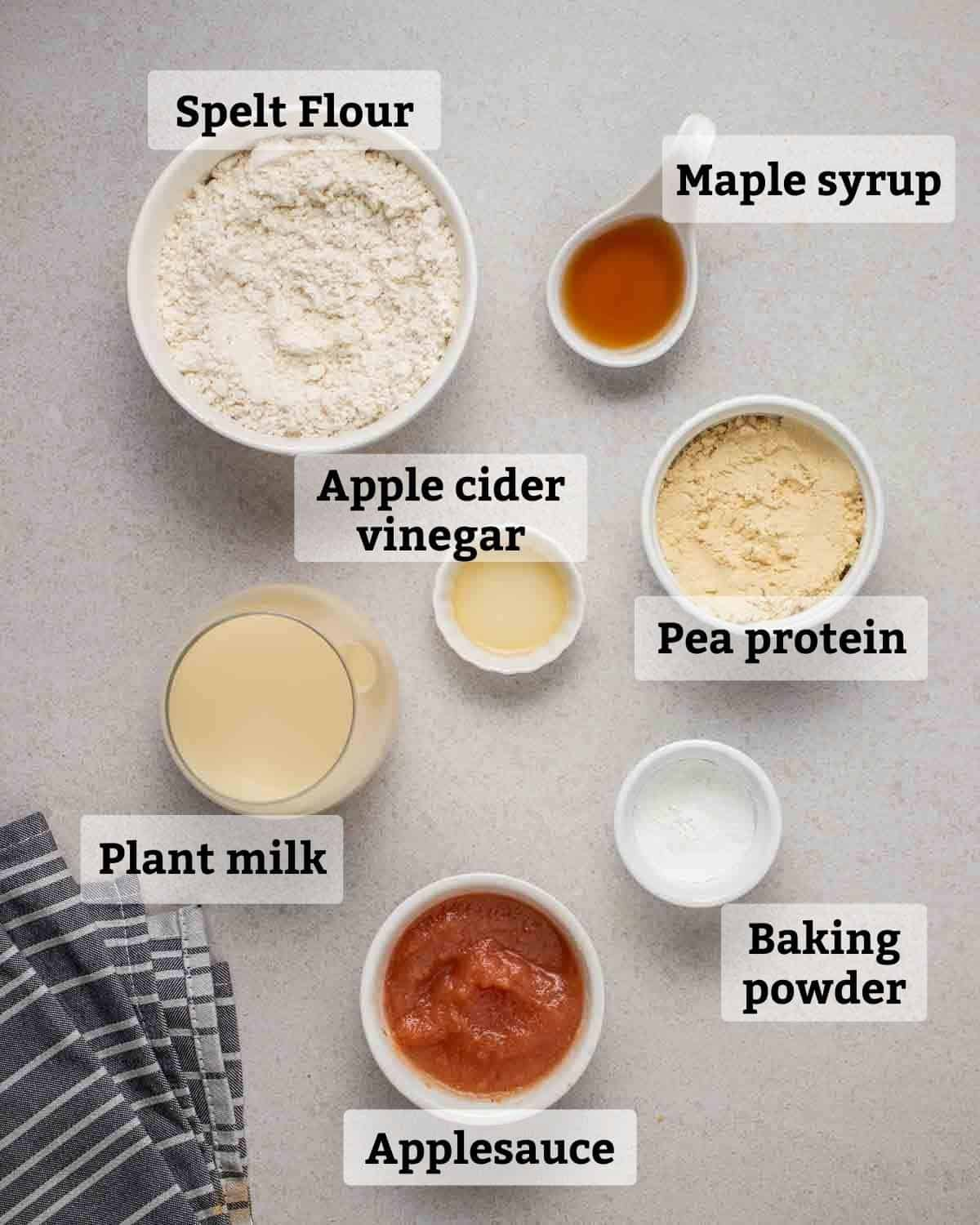 Ingredients needed like spelt flour, pea protein, milk and applesauce on a grey background.