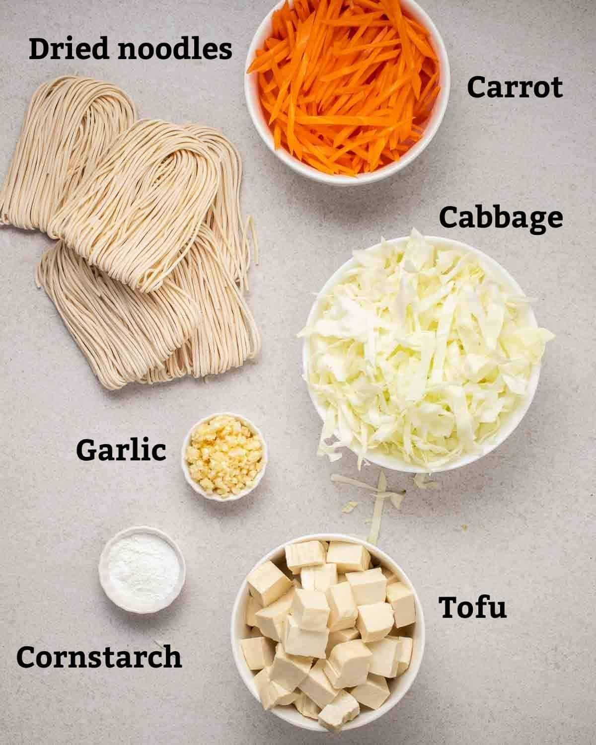 Ingredients needed for peanut noodles like dried noodles, garlic, tofu, cornstarch and vegetables on a grey background.
