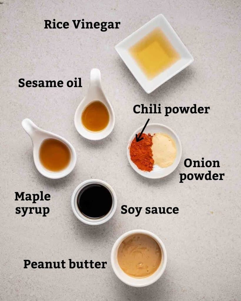 Ingredients needed for peanut sauce like sesame oil, soy sauce, peanut butter and other seasonings on a grey background.