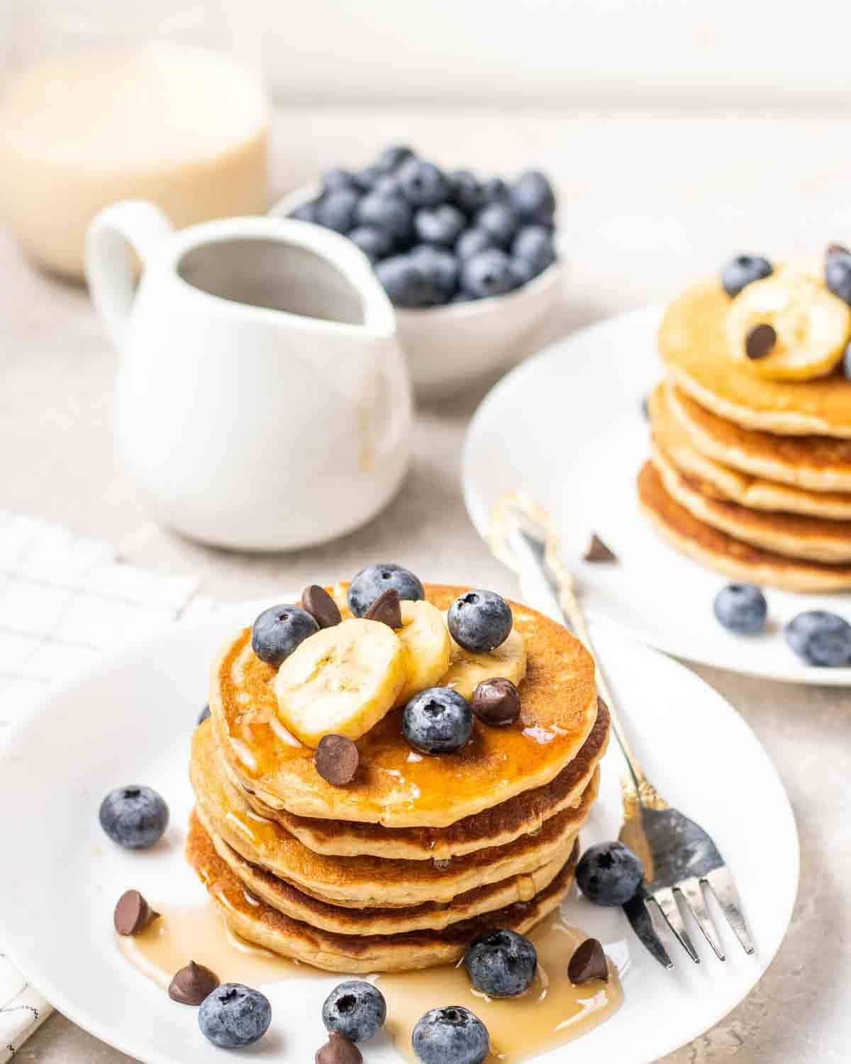 2 stacks of pea protein pancakes topped with fruits with bowl of blueberries and glass of milk in the background.