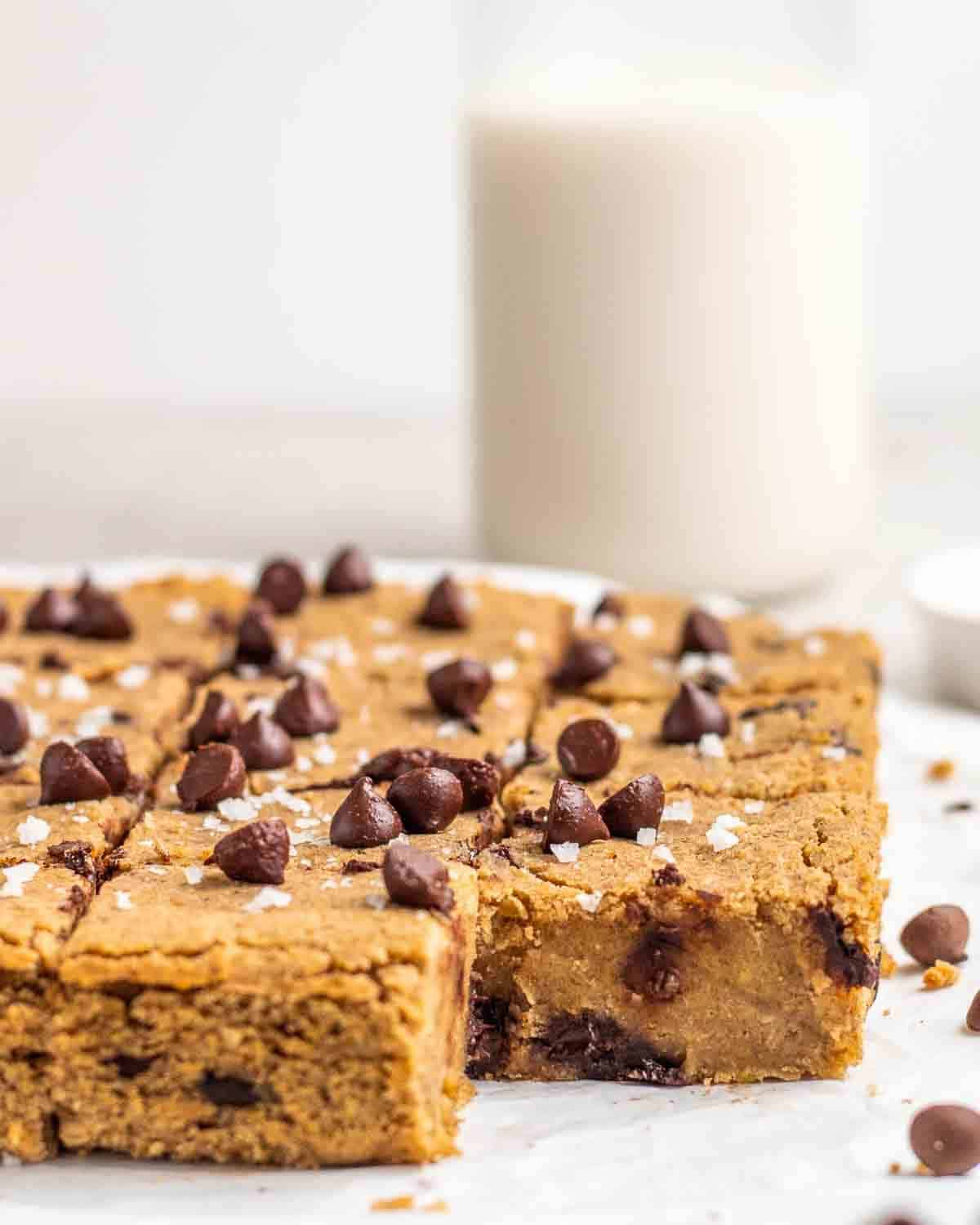A tray of sliced chickpea blondies with chocolate chips and a jar of milk in the background.