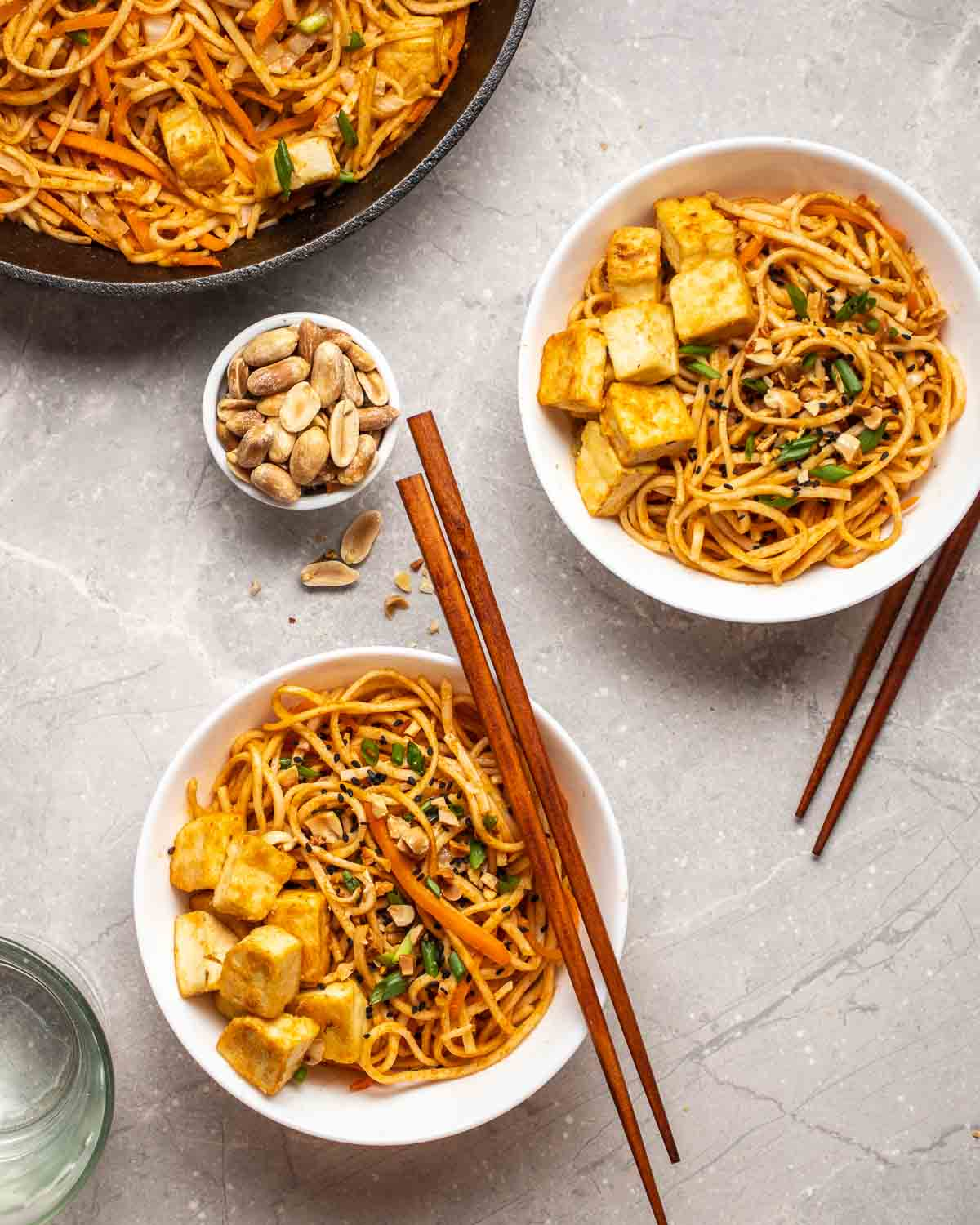 2 bowls of peanut noodles served with chopsticks with dish of peanuts and a pan filled with noodles in the background.