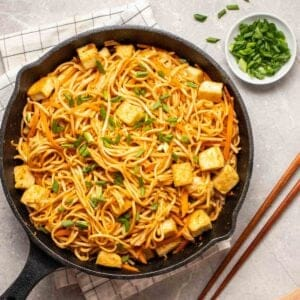 Peanut noodles in skillet topped with chopped scallions and sesame seeds.