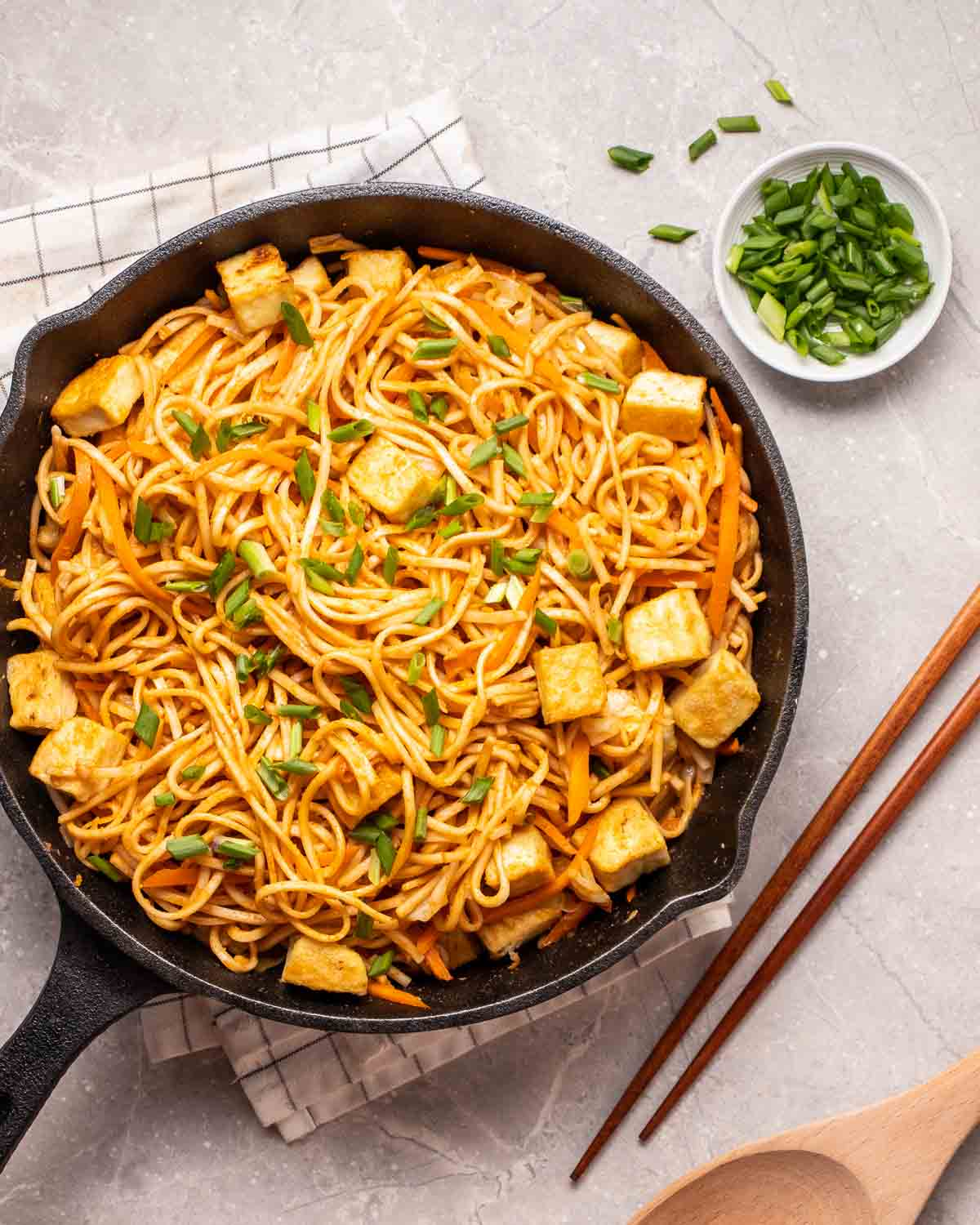 Peanut noodles in a cast iron skillet with dish of chopped skillet and pair of chopsticks beside.