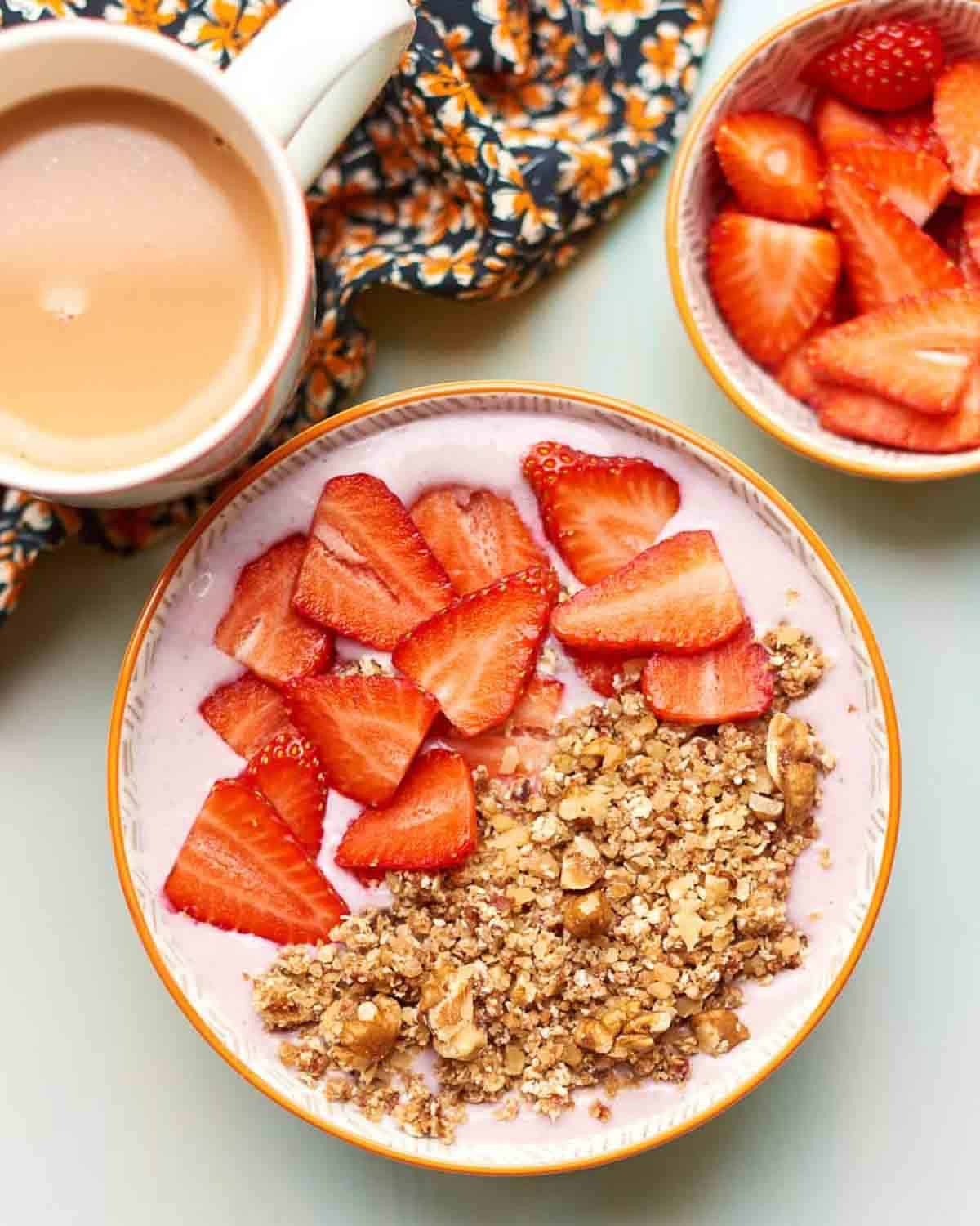 Strawberry breakfast bowl topped with strawberries and granola with tea and a bowl of strawberries beside.