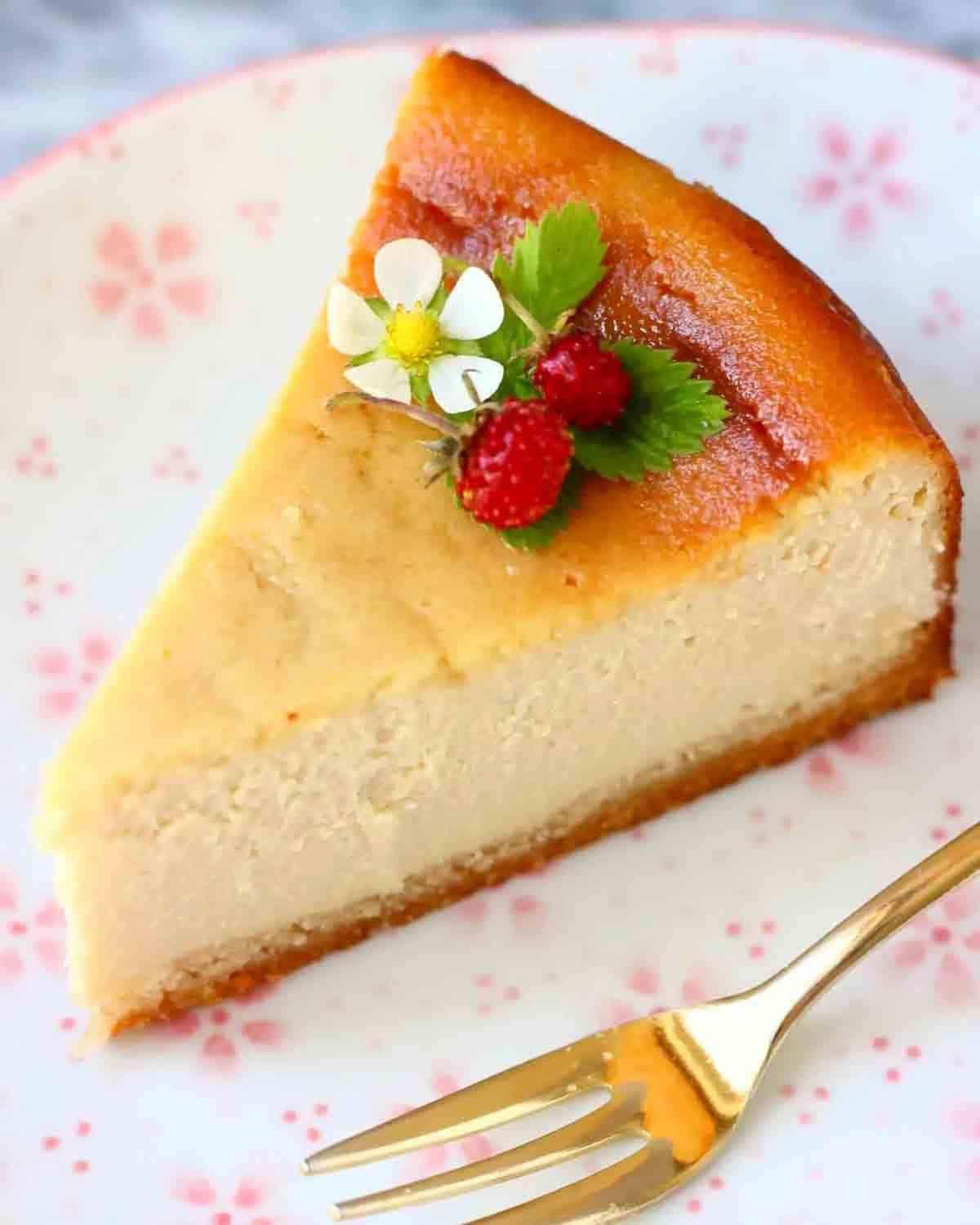 A slice of cheesecake on a white and pink floral plate with a fork.