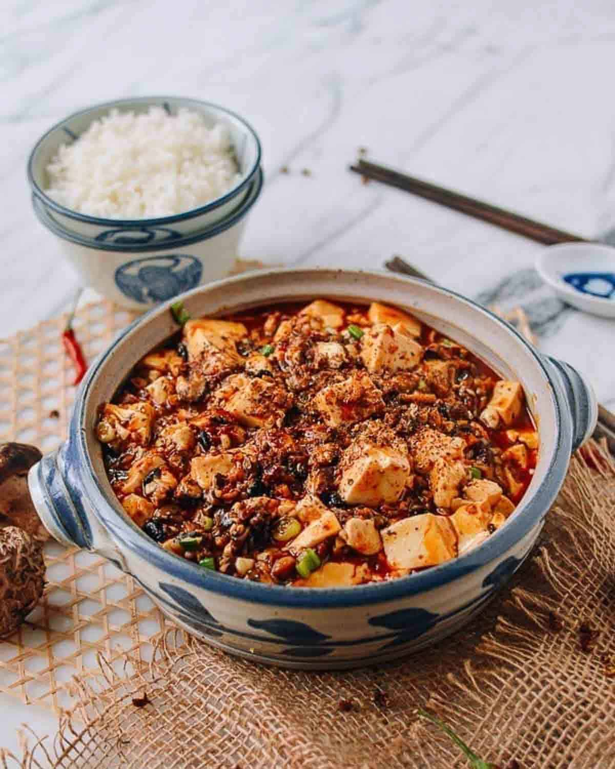 A pot of mapo tofu with a bowl of rice and chopsticks in the background.