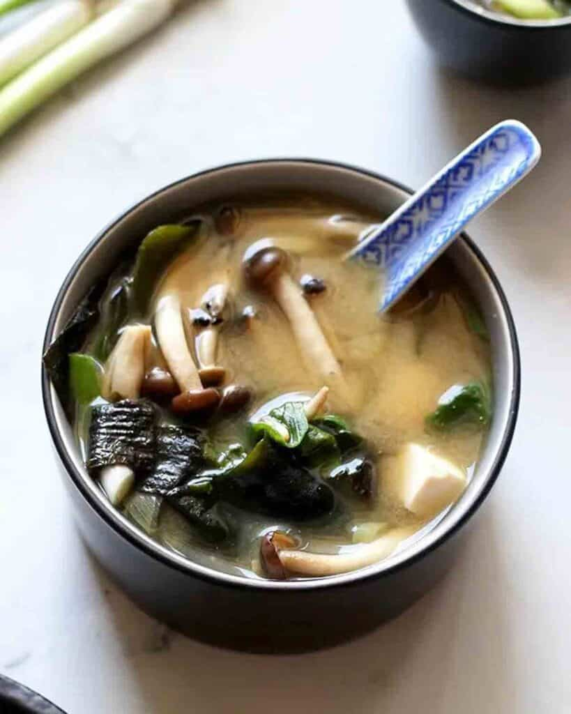 A bowl of miso soup with a ceramic spoon.