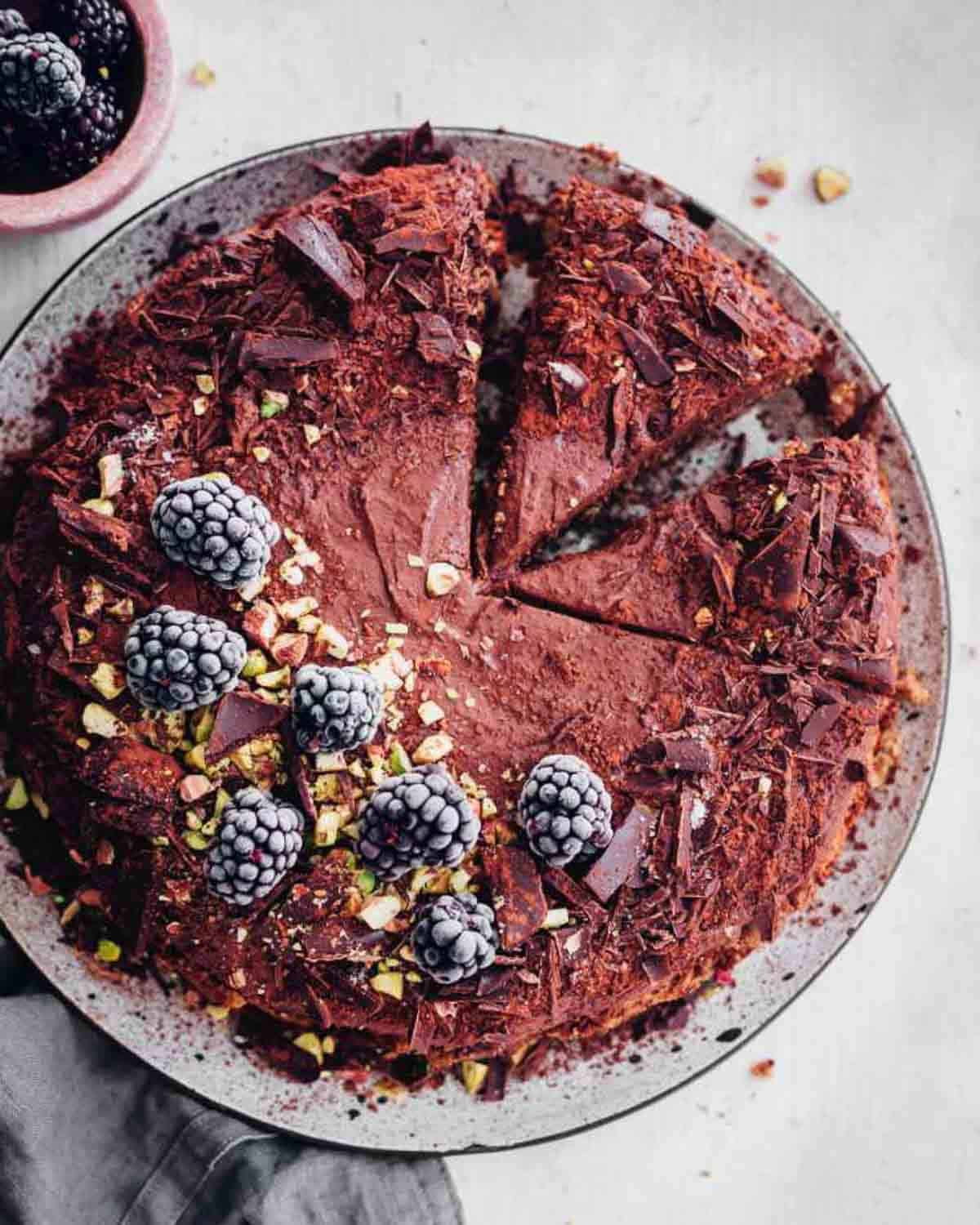 Mousse cake that is partially sliced topped with frozen blackberries and shredded chocolate.