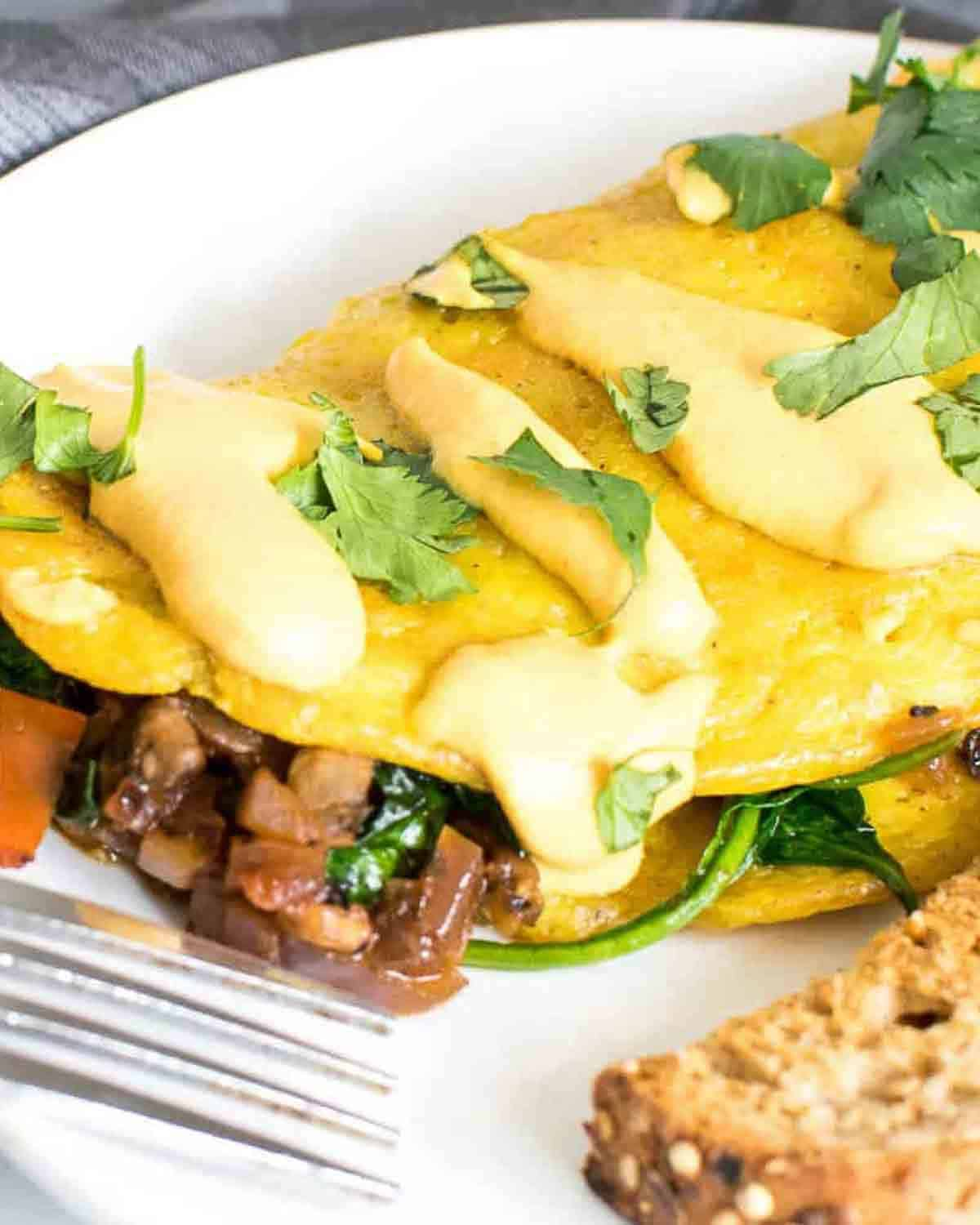 Omelette filled with mushrooms and spinach with a fork.