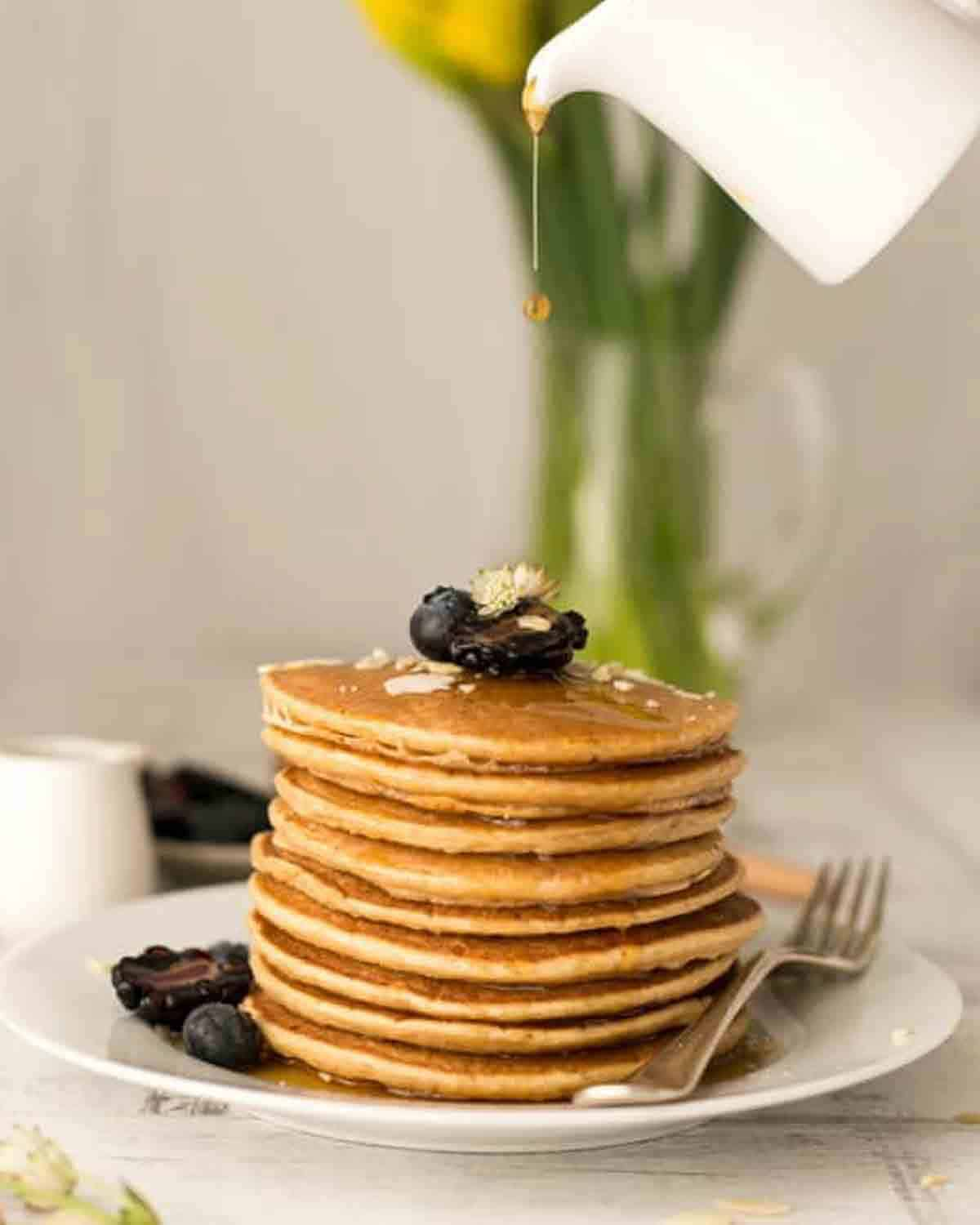 Pouring maple syrup over a stack of pancakes topped with blueberries with a fork.