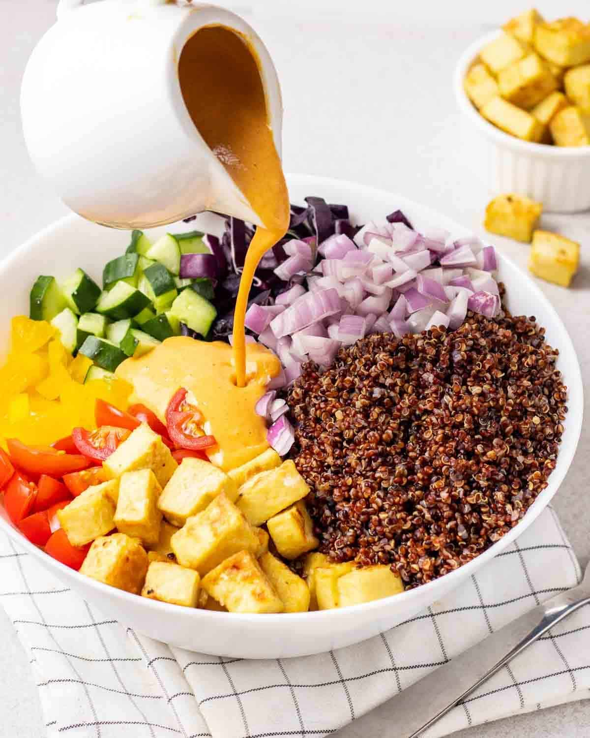 Pouring curry dressing into a bowl of salad.
