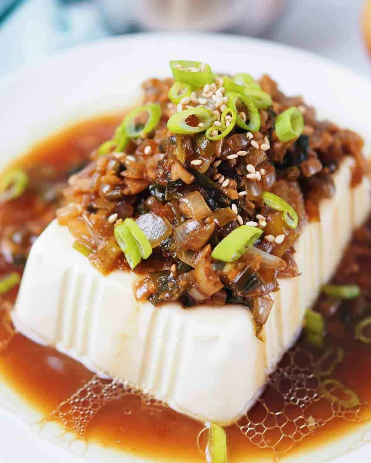Tofu served on a whit plate topped with chopped scallions and sesame seeds.