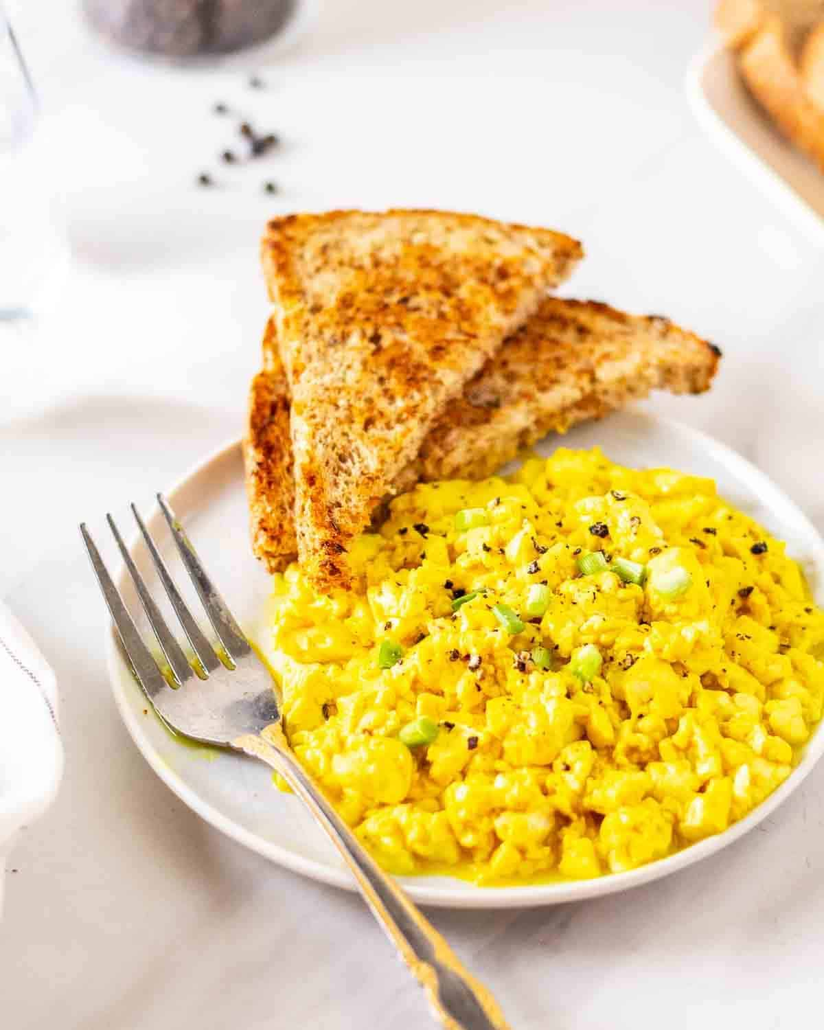 Tofu scramble served with toast on a plate with a fork.