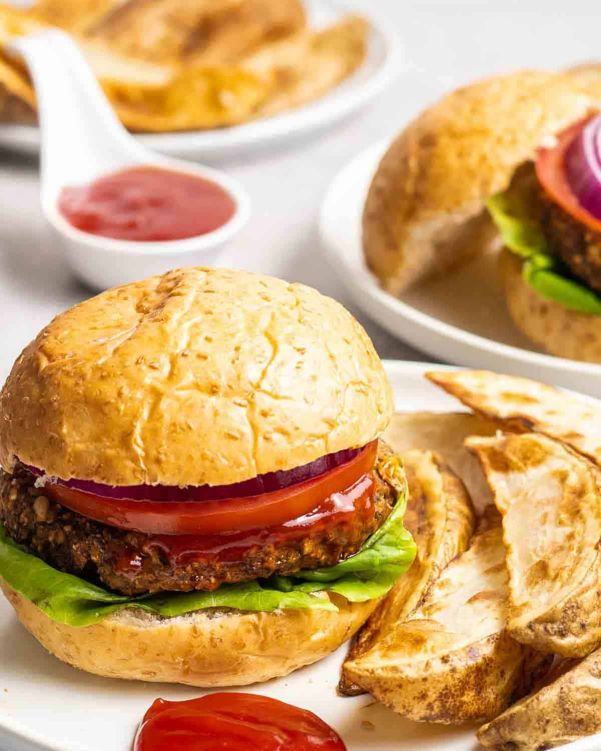 Burger served with a side of potato wedges in a white plate with dish of tomato sauce in the background.