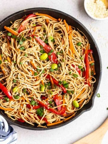 Teriyaki soba noodles in a pan with a dish of sesame seeds, scallions and a wooden spatula beside.