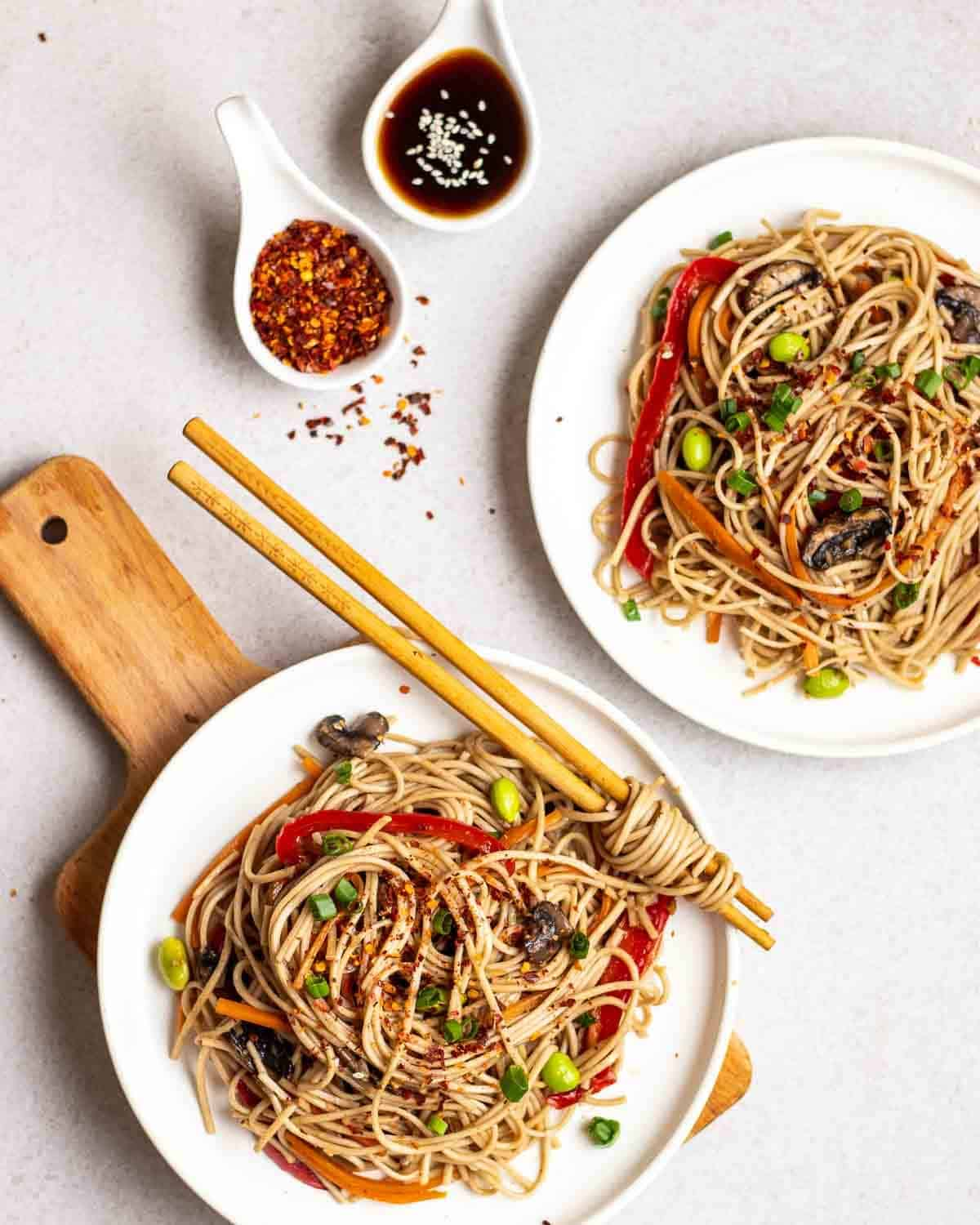 2 plates filled with stir-fry soba noodles with chopsticks. There is some chili flakes and soy sauce beside them.