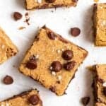 Few slices of blondies arranged on a parchment paper with chocolate chips in the background.
