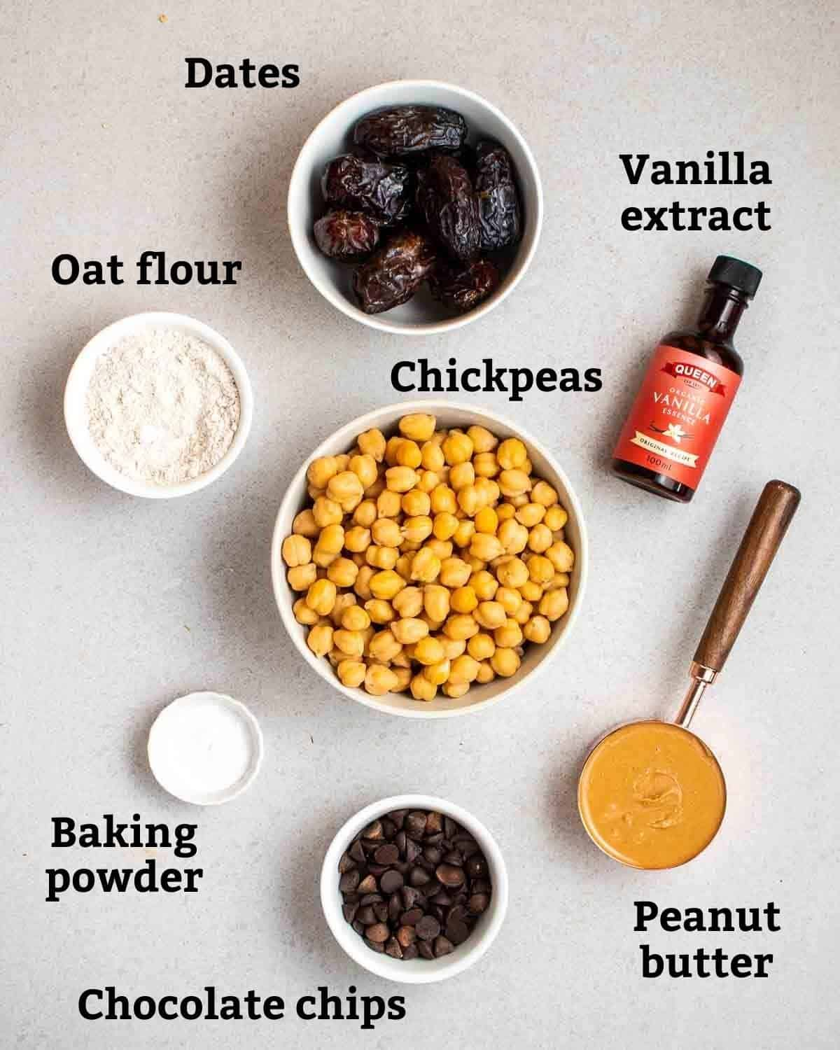 Ingredients needed like chickpeas, peanut butter, dates and oat flour on a grey background.