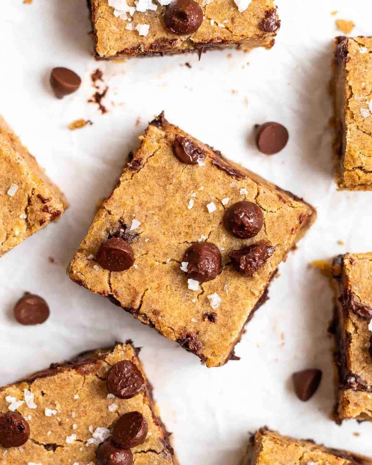 Chickpea blondies arranged on a parchment paper topped with chocolate chips and salt flakes.