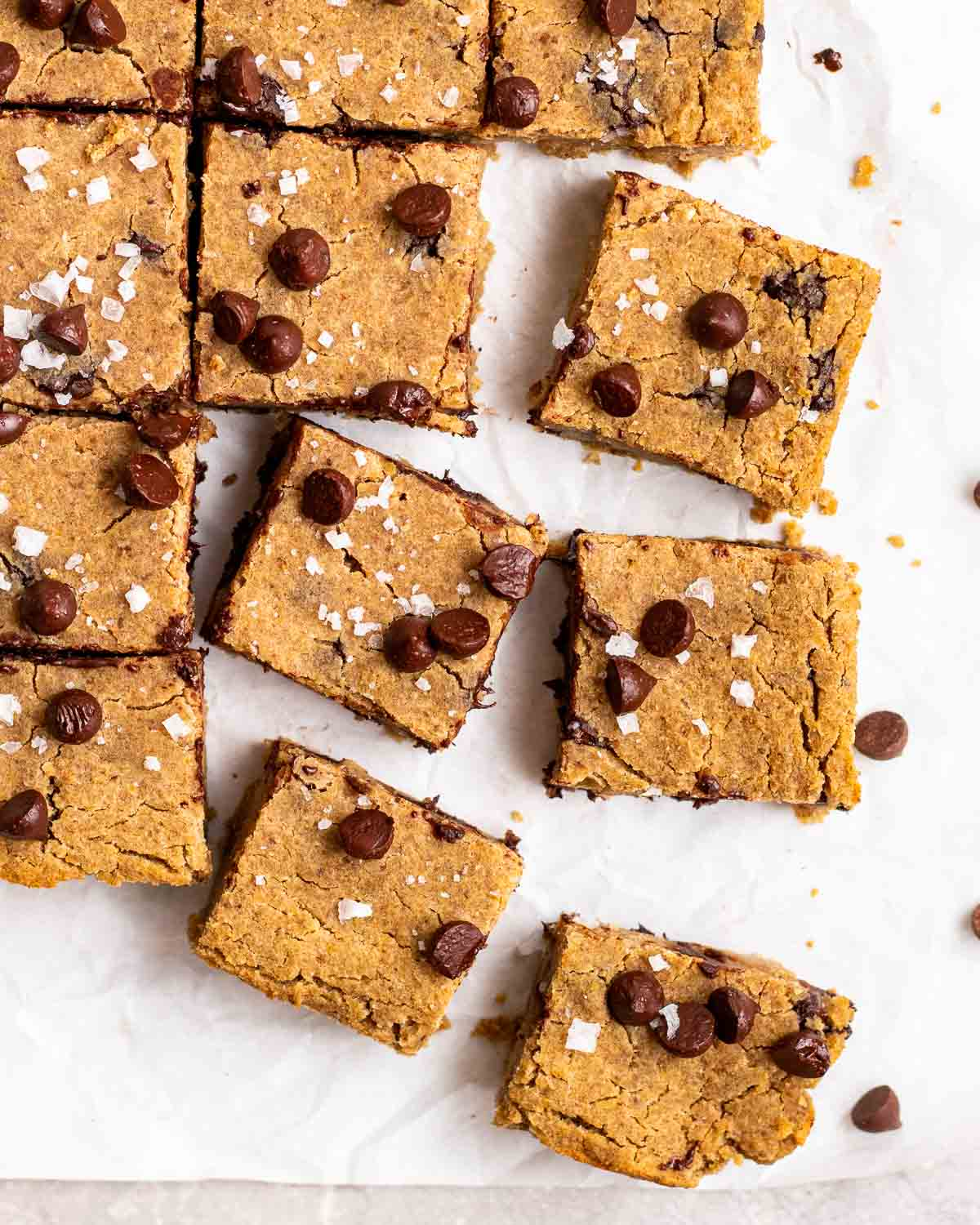 A tray of peanut butter blondies arranged on a parchment paper topped with sea salt flakes.