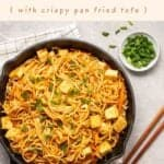 Peanut noodles in a cast iron pan topped with tofu cubes and chopped scallions with text on the upper half.