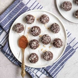 Protein balls arranged on a white plate with a teaspoon filled with cocoa powder beside.
