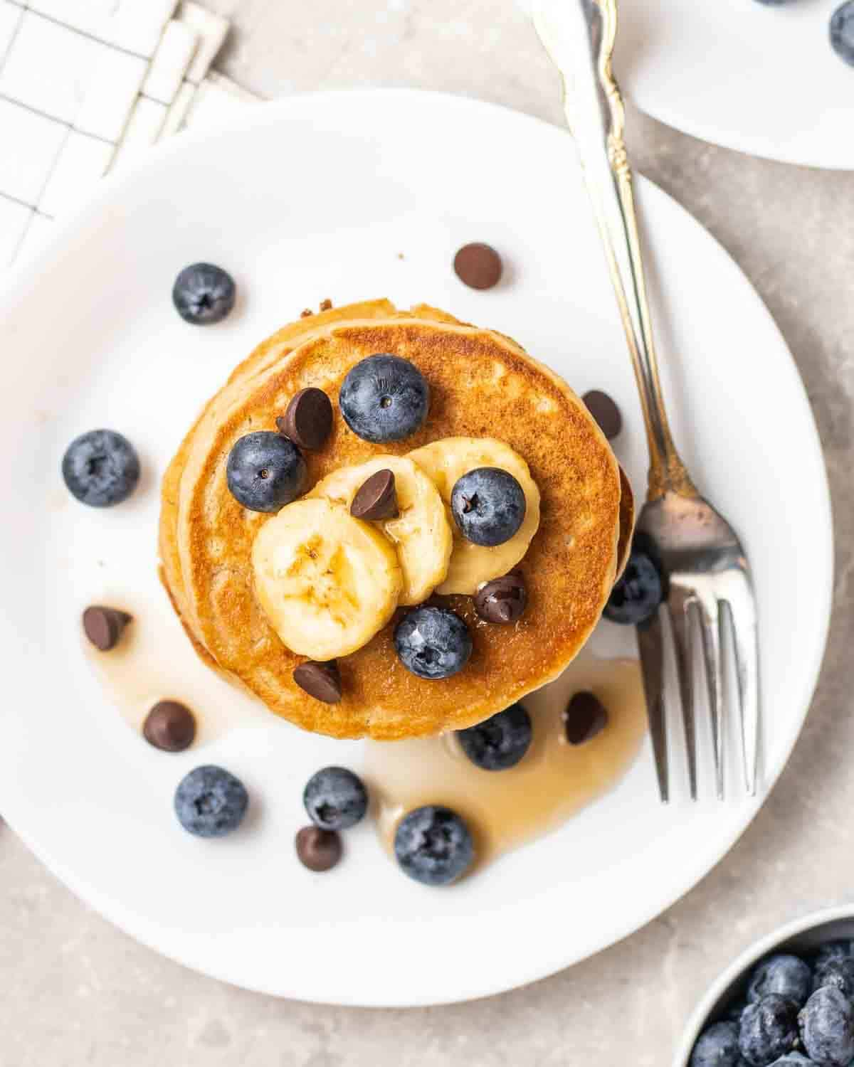 Pancakes on a white plate with a fork topped with blueberries, bananas and chocolate chips.