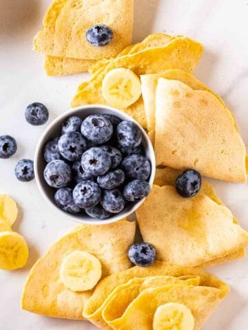 Folded crepes arranged around a bowl of blueberries.