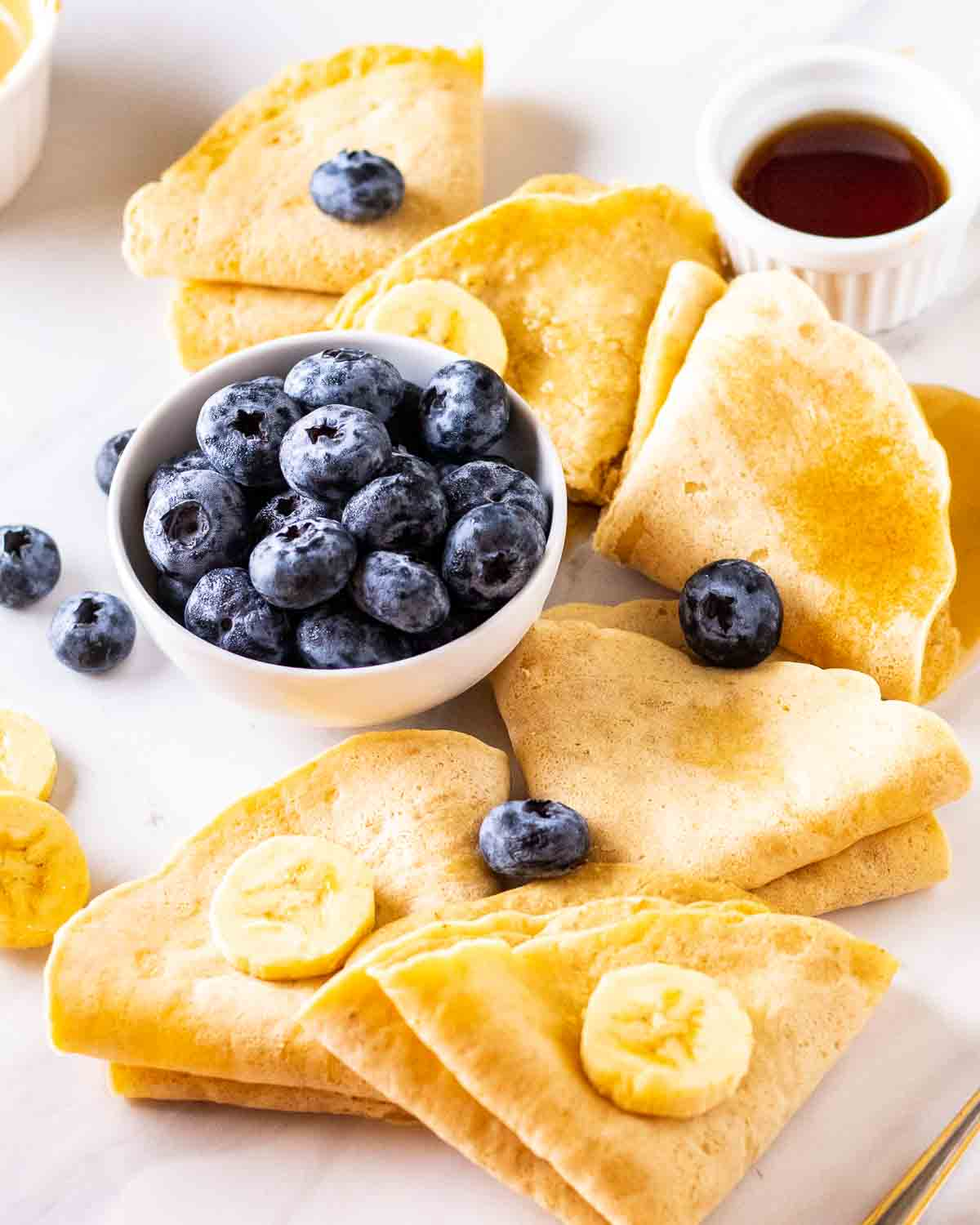 Folded crepes topped with banana and blueberries with maple syrup and bowl of blueberries beside.