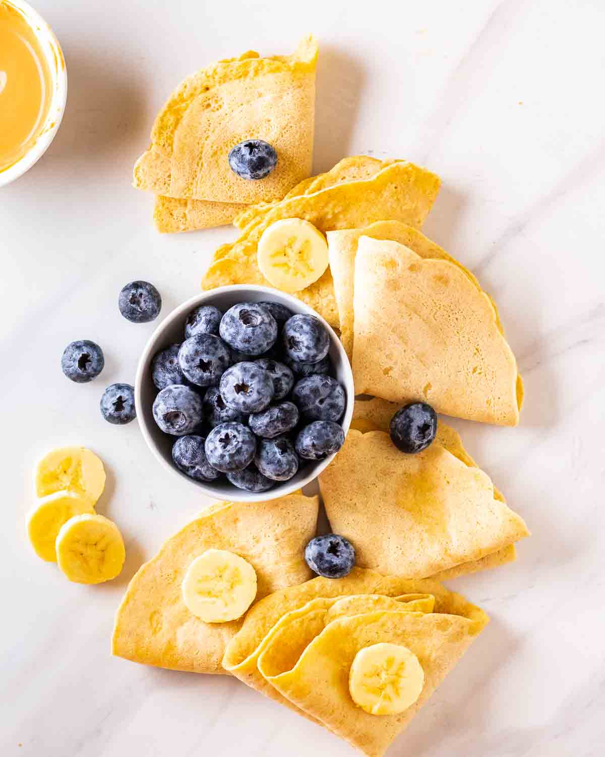 Folded crepes arranged on a white background topped with blueberries and sliced banana.