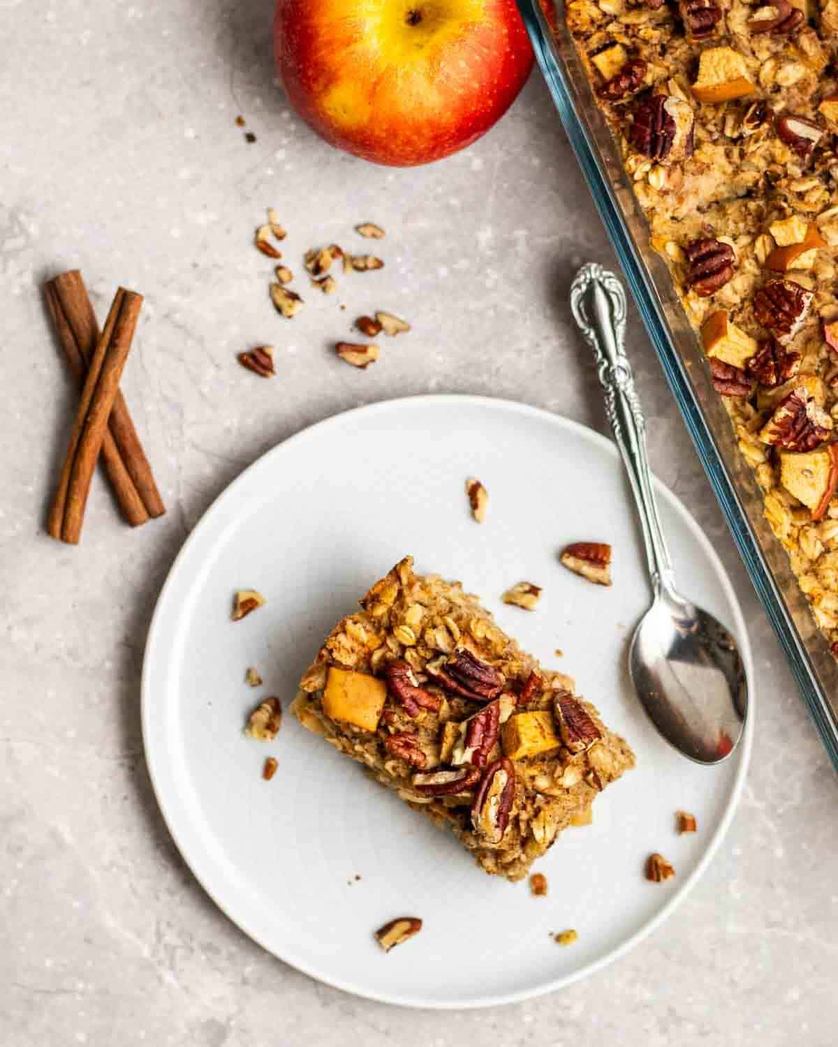 A slice of baked oatmeal on a plate with spoon with cinnamon sticks and chopped pecans beside.