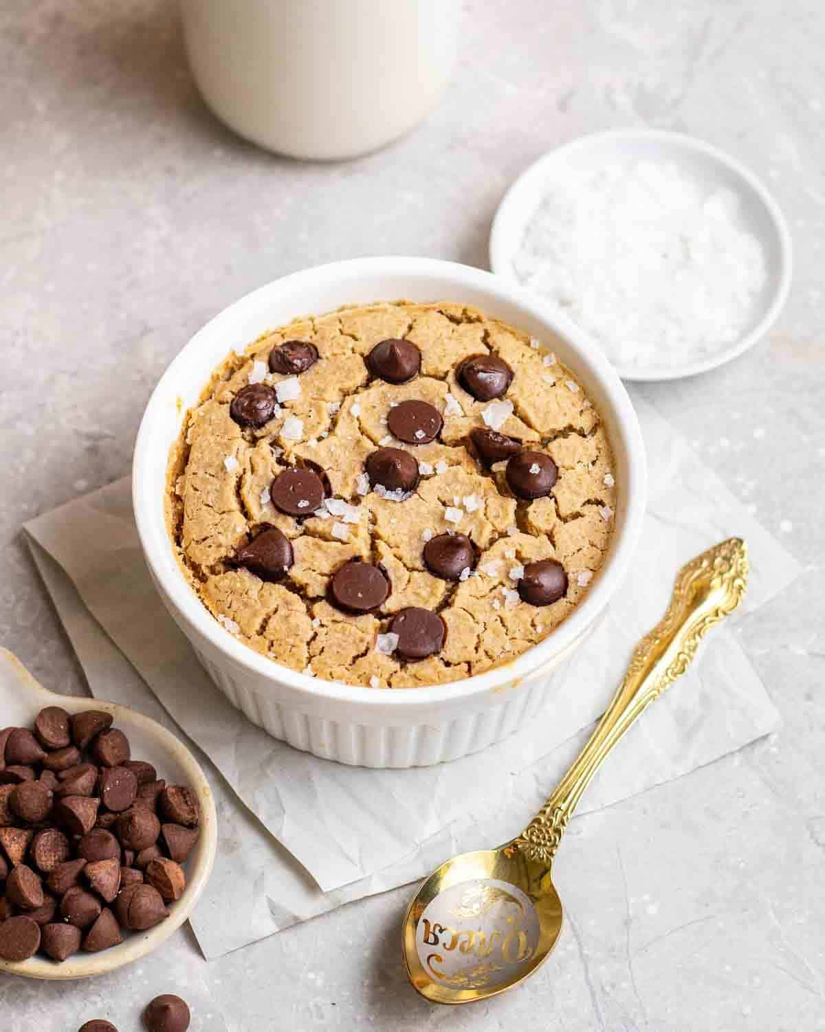 Baked oats in a white ramekin with spoon, chocolate chips, salt flakes and a jar of milk in the background.