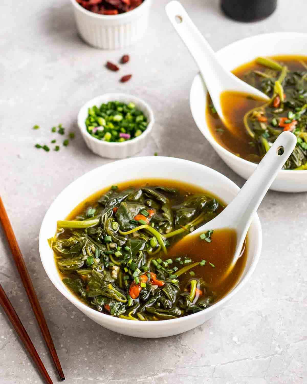 2 bowl of spinach soup served with spoon with chopsticks, chopped scallions and soy sauce in the background.