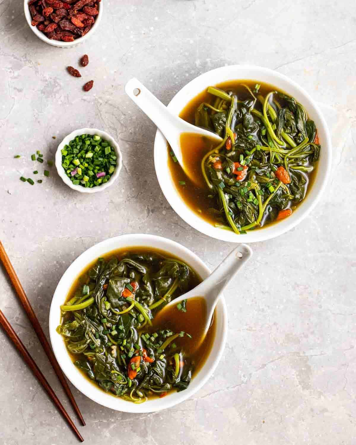 2 bowls of spinach soup with spoons. There are chopsticks, goji berries and scallions beside.