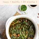 Spinach soup in a ceramic pot with chopped scallions and soy sauce beside with text on the upper half.