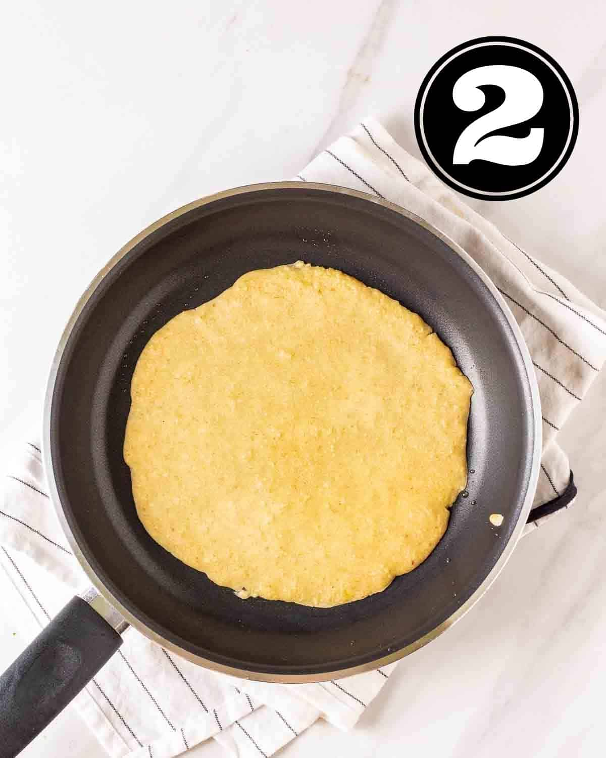 Cooking crepes in a black pan on a white teacloth.