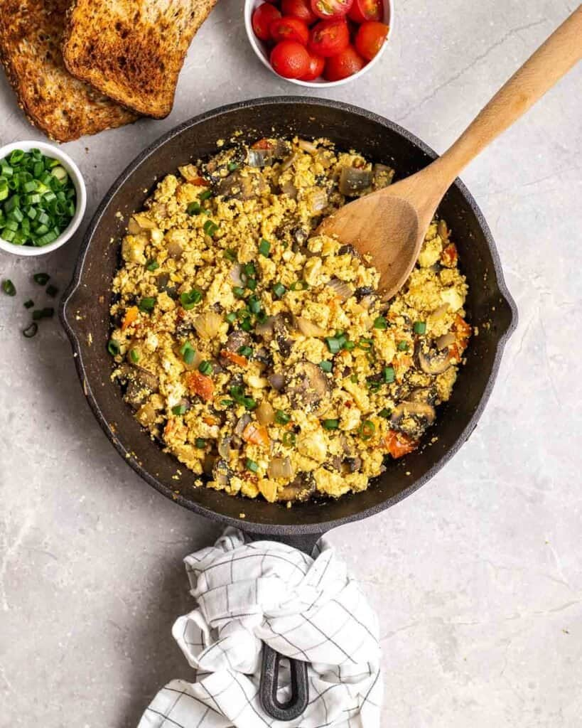 Tofu scramble in a cast iron skillet topped with scallions with a wooden spatula.