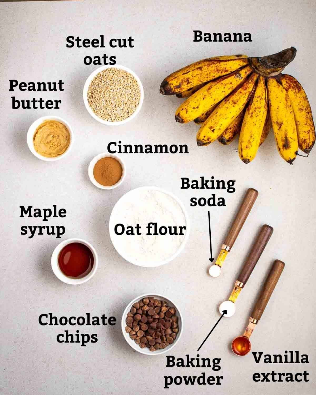 Ingredients needed like steel cut oats, oat flour, banana and peanut butter on a grey background.