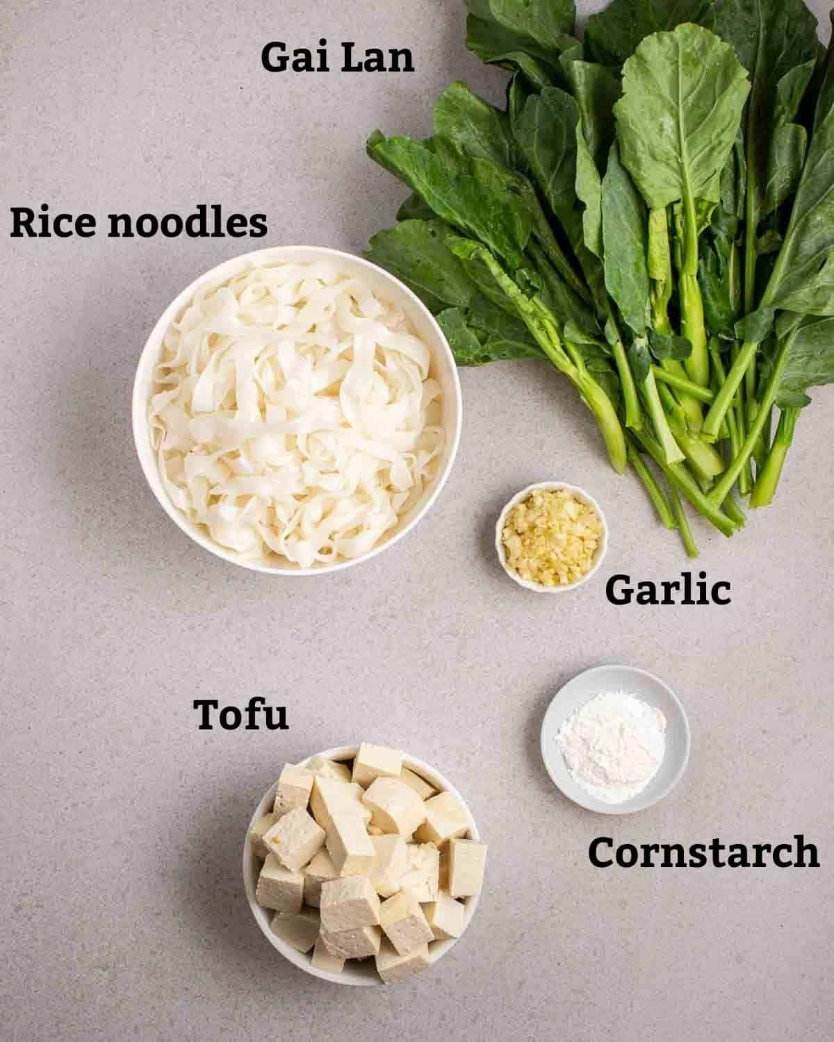 Ingredients needed like gai lan, rice noodles, tofu, garlic and cornstach on a grey background.