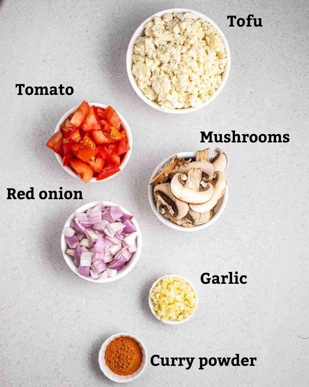 Ingredients needed like tofu, tomato, mushrooms, onion, garlic and curry powder.