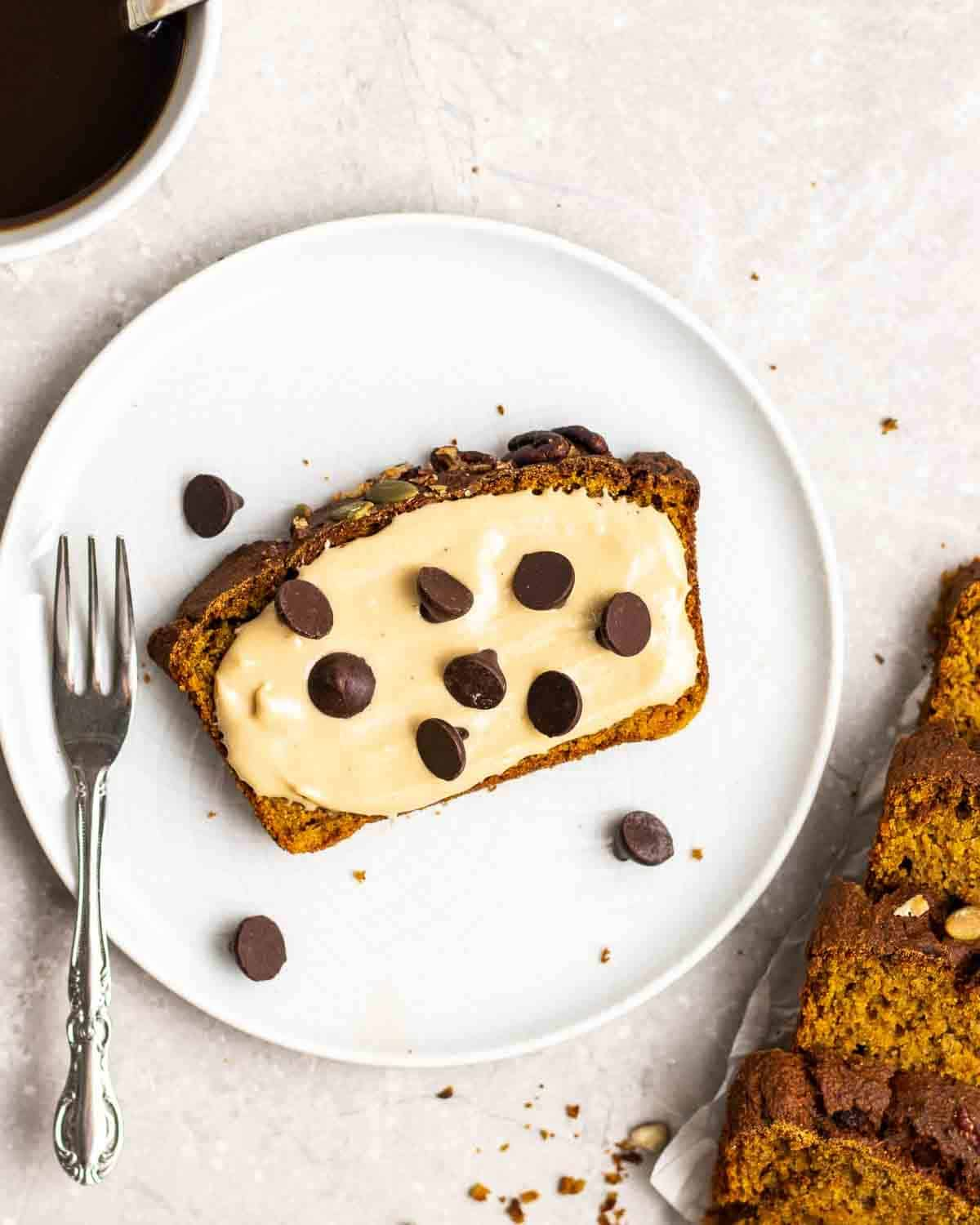A slice of pumpkin banana bread on a plate topped with cashew butter and chocolate chips with a fork beside.