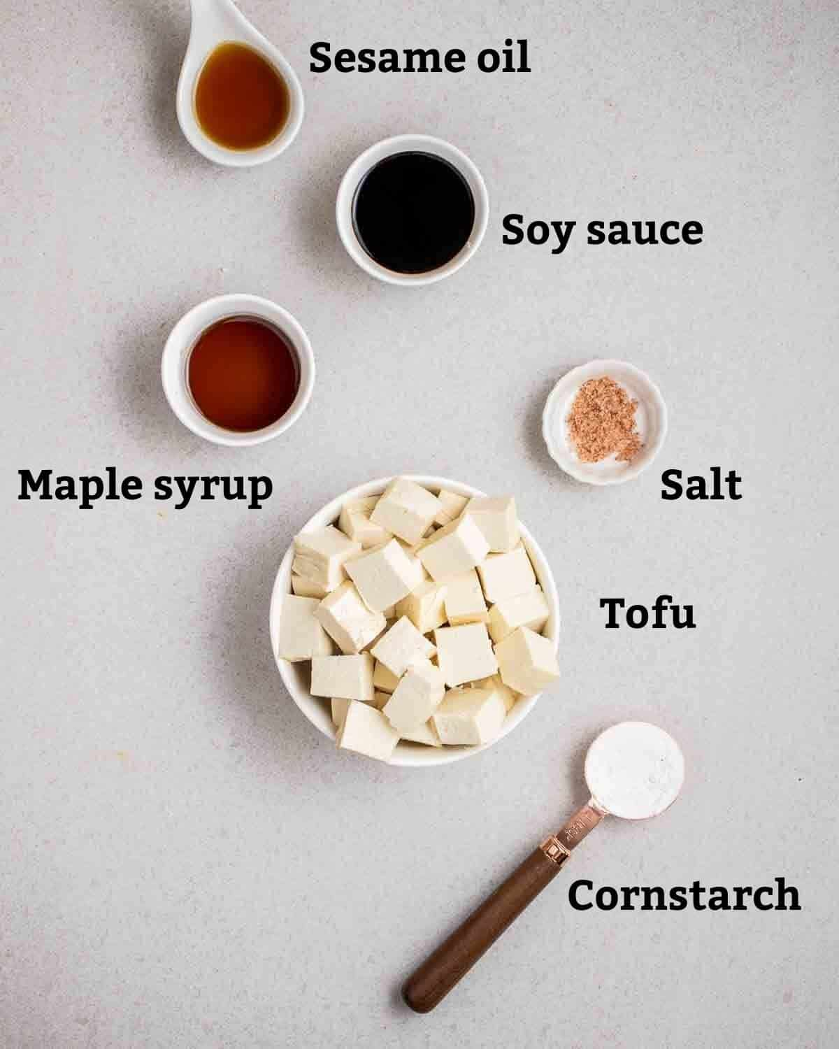 More ingredients needed for japchae like tofu, cornstarch, maple syrup, soy sauce and sesame oil on a grey background.