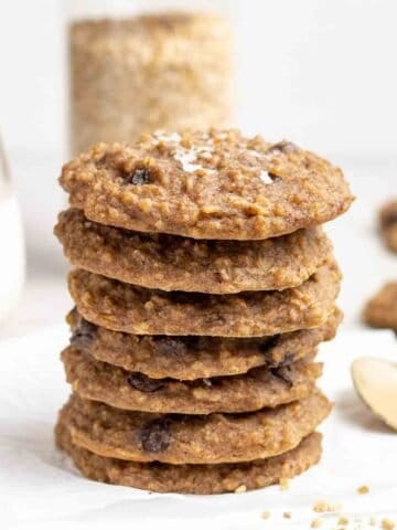 A stack of cookies with jar of steel cut oats, milk and spoonful of peanut butter in the background.