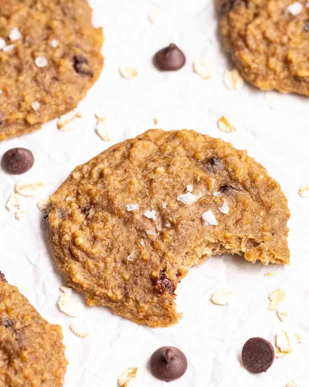 A cookie with a bite taken out on a parchment paper with oats and chocolate chips in the background.