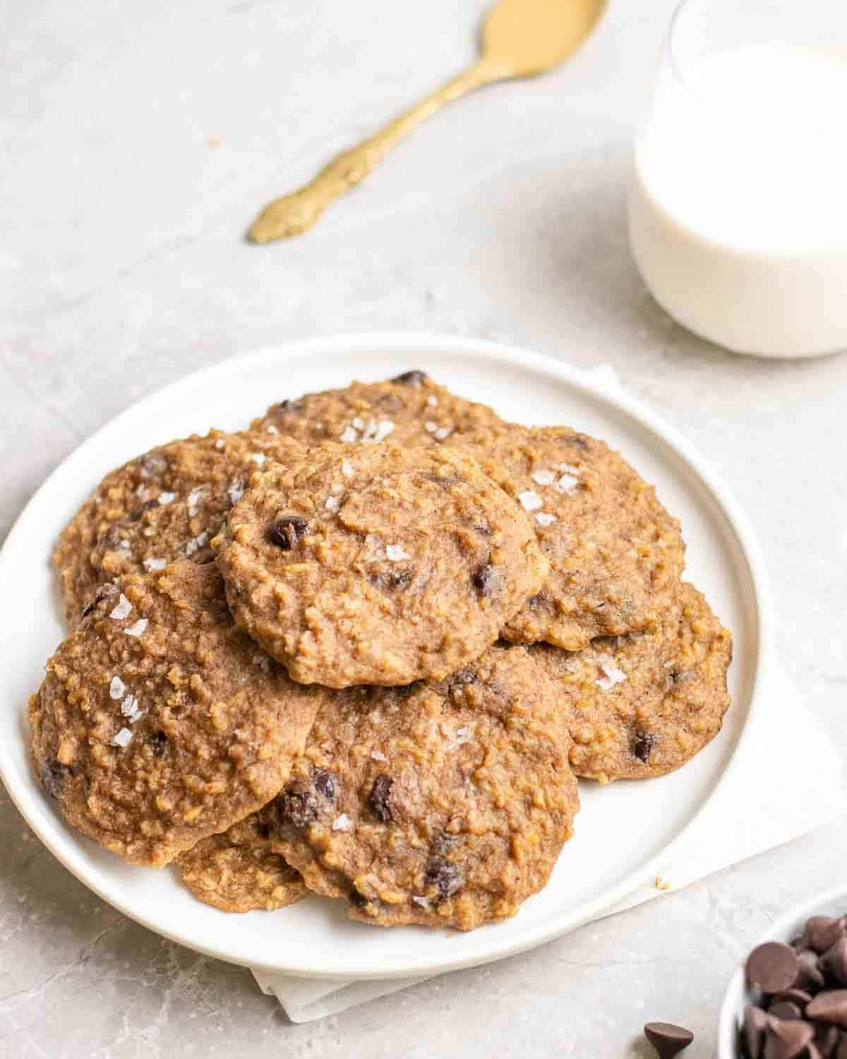 A plate of cookies with milk, chocolate chips and spoonful of peanut butter in the background.