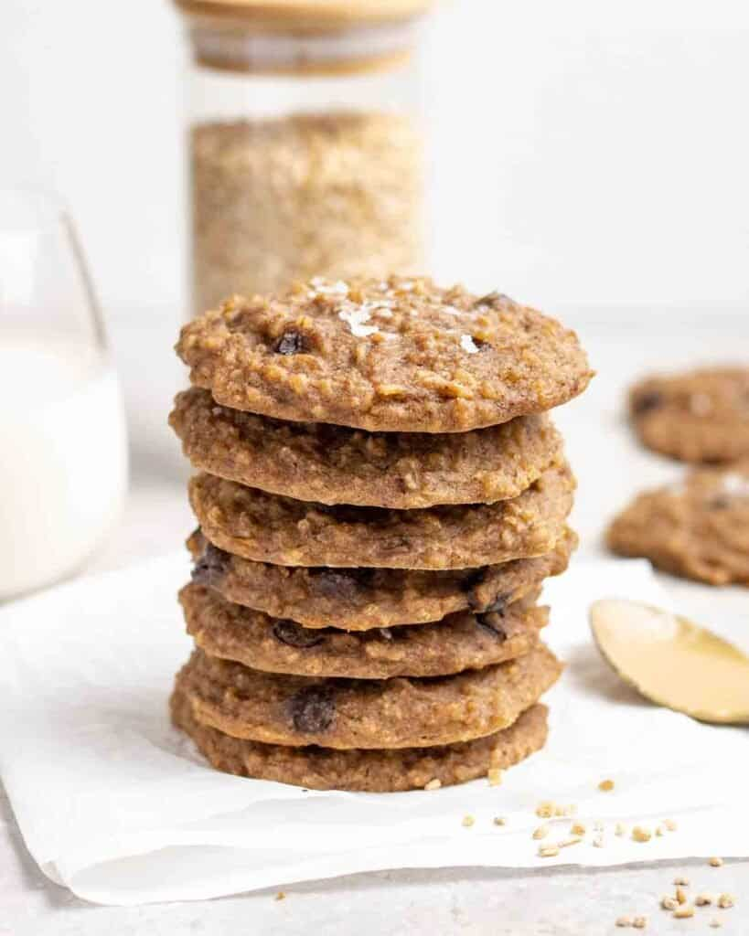 A stack of cookies with jar of steel cut oats, milk and spoonful of peanut butter behind.