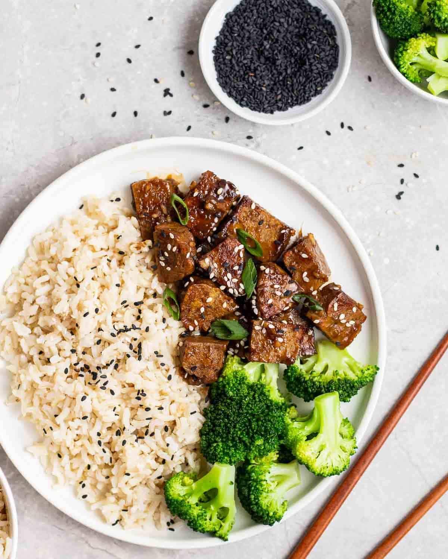Teriyaki seitan served with brown rice and broccoli on a plate with chopsticks beside.