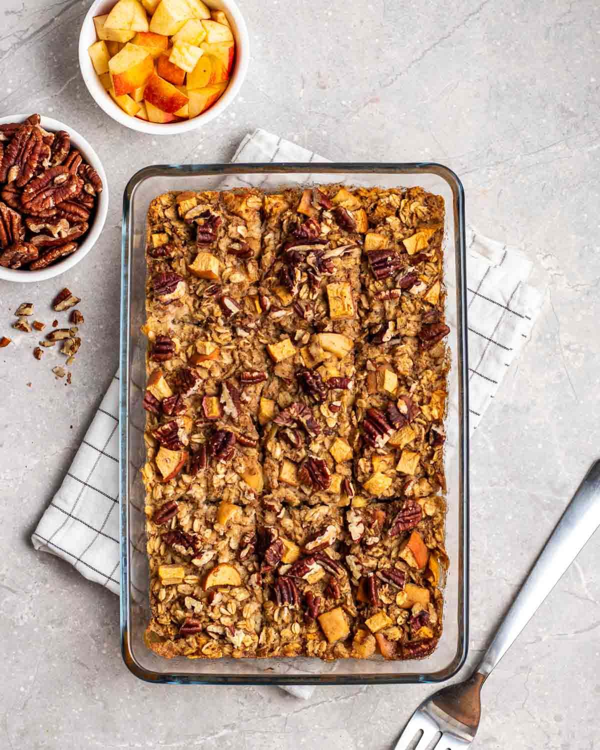 Apple baked oatmeal in a glass dish with chopped apples, pecans and a fork beside.